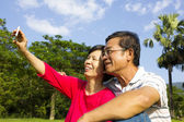 Senior couple sitting on grassland and  taking picture — Stock Photo
