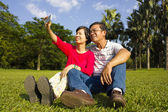 Asian Senior couple sitting on grassland and  taking picture  — Stock Photo