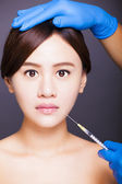 Asian beautiful woman gets injection into her mouth. aesthetic m — Stock Photo