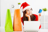Beautiful young woman holding credit card with laptop. Christmas — 图库照片