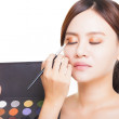 Makeup artist applying colorful eyeshadow on model's eye with a — Stock Photo #56605255