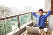 Relaxed young business man watching the city view — Stock Photo