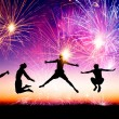 Happy young people jumping on the hill with firework background — Stock Photo #58933531