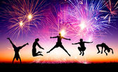 Happy young people jumping on the hill with firework background — Stock Photo