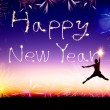 Young man jumping and drawing the happy new year — Stockfoto #59067833
