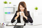 Beautiful young business woman drinking coffee in office — 图库照片