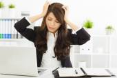 Stressed  businesswoman sitting in office — Stock Photo