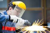 Worker with grinder machine cutting metal in factory — Stock Photo
