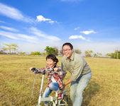 Happy Father teaching little girl to ride bicycle — Stock fotografie