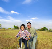 Happy Father teaching his daughter to ride bicycle — Stock Photo