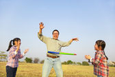 Happy family playing with hula hoops outdoors — Stock Photo