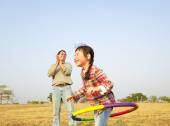 Happy little girl playing  hula hoops outdoors — Stock Photo