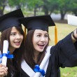 Two happy women in graduation gowns taking picture with cell pho — Stock Photo #65843957