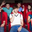 Young men talking on the phone while watching movie at the cinem — Stock Photo #65844263