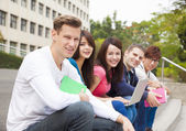 Happy  young group of students sitting on the stair — Stock Photo
