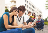Young couple student using the tablet — Stock Photo