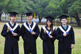 Happy students in graduation gowns on university campus — Stock Photo