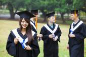 Happy students in graduation gowns on university campus — ストック写真