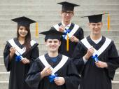 Young students in graduation gowns on university campus — Stock Photo