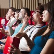 Happy Young people  watching a movie at the cinema — Stock Photo #66914347