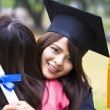 Young female graduate hugging her friend at graduation ceremony — Stock Photo #66914587