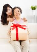 Happy mother and daughter with gift box — Stock Photo