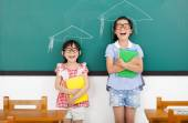 Happy little girls with graduation concept in classroom — Stock Photo