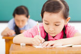 Children in classroom with pen in hand — Stock Photo