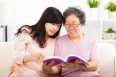 Happy mother and her daughter reading book — Stock Photo