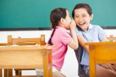 Happy little girls whispering and sharing a secret  in classroom — Stock Photo
