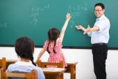 Teacher asking question with children  in classroom — Stock Photo