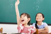 Happy school children  raised hands in class — Stock Photo