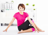 Beautiful young woman stretching on the floor  — Stock Photo