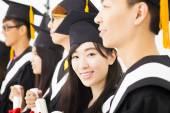 Asian female college graduate at graduation with classmates — Stock Photo