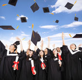 Happy students throwing graduation caps into the Air — Stock Photo