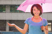 Beautiful young woman under pink umbrella — Stock Photo