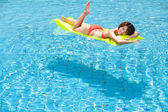 Young woman relaxing in swimming pool — Stock Photo