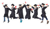 Happy  student group in graduate robe jumping together — Stock Photo