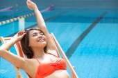 Young woman relaxing in  chair beside swimming pool — Stock Photo