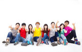 Happy young group sitting together with thumb up — Stock Photo