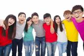 Young student group  with arms around each others shoulders — Stock Photo