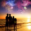 Happy family watching the sunset and firework on the beach — Stock Photo #75482075