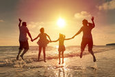 Happy family jumping together on the beach — Stock Photo