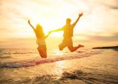Young happy couple jumping on beach  — Stock Photo