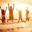 Group of happy young people jumping on the beach — Stock Photo #76081921