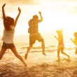 Group of happy young people dancing on the beach — Stock Photo #76081961