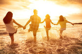 Group of happy young people playing on the beach — Stock Photo