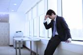 Depressed young businessman in office — Stock Photo