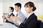 Business people sitting in a row and applauding — Stock Photo