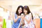 Happy woman looking at smart phone at  shopping mall — Stock Photo